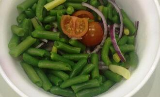 Шаг 6: В салатник выложите помидоры, лук и стручковую фасоль. Добавьте соус.