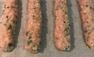 Шаг 7: Сформируйте из фарша продолговатые колбаски длиной 20 см. Положите на противень и выпекайте в разогретой до 180-200 градусов духовке около 15-20 минут. После переверните на другую сторону и готовьте около 15 минут.