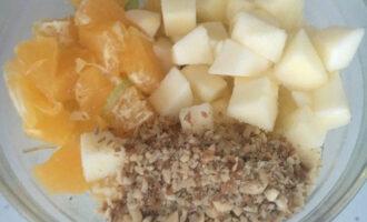 Шаг 6: Выложите в салатник сельдерей. Добавьте яблоко, грецкие орехи и кусочки апельсина.
