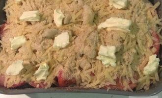 Шаг 8: Вылейте в форму, смазанную маслом, томатный соус. Четвертинки помидоров выложите по краям, а вареную цветную капусту в центре. Посолите, поперчите и посыпьте смесью из сыра с сухарями. Разложите кусочки сливочного масла и поставьте в разогретую  до 180 градусов духовку на 30 минут.