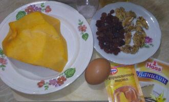 Шаг 1: Подготовьте необходимые продукты: тыкву, цельнозерновую муку, яйцо, орехи, изюм, ванилин, разрыхлитель и соль.