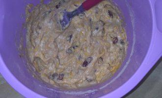 Шаг 4: Добавьте муку, разрыхлитель, ванилин, нарезанные орехи и изюм. Тщательно перемешайте.