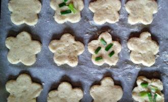 Шаг 6: Из раскатанного теста вырежьте печенье произвольной формы. Выложите печенье на бумагу для выпечки и смажьте растительным маслом. По желанию посыпьте зеленью. Выпекайте в духовке при температуре 200 градусов 15 минут.