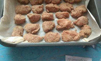 Шаг 7: Противень застелите бумагой для выпечки. Выложите кусочки курицы и отправьте в духовку на 15-20 минут.