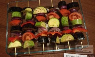 Шаг 8: На деревянные шпажки наберите овощи чередуя. Уложите в огнеупорную посуду. Желательно, чтобы у Вашей формы были высокие бортики, на которых можно разместить шпажки с овощами. Отправьте шашлычки в нагретую до 200 градусов духовку. Запекайте 35-40 минут до готовности.
