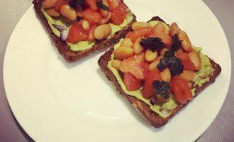 Шаг 7: На хрустящий ломтик хлеба намажьте гуакамоле, затем присыпьте немного лука, сверху добавьте пару столовых ложек белой фасоли с помидором и украсьте кинзой.