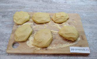 Шаг 3: На доску посыпьте немного кукурузной муки. Руки смажьте растительным маслом. Из теста сформируйте лепешки 1-1,5 сантиметра толщиной, котлетной формы.