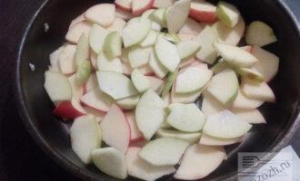Шаг 2: Яблоки нарежьте тонкими дольками и разложите по дну формы, застланной пекарской бумагой.