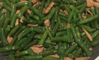 Шаг 4: К грибам добавьте стручковую фасоль и немного оливкового масла и дальше продолжайте жарить, помешивая.