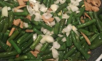 Шаг 5: Почистите и нарежьте лук и отправьте его на сковороду к грибам и фасоли. Продолжайте жарить еще 15-20 минут. Добавьте соевый соус.