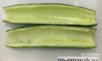 Шаг 2: Для этого блюда удобно использовать длинный огурец. Обрежьте кончики огурца. Разрежьте вдоль пополам. При помощи чайной ложки удалите семена и мякоть огурца.