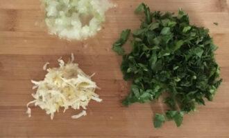 Шаг 4: На мелкой терке натрите лук и чеснок. Зелень (укроп и петрушку) мелко нарежьте.