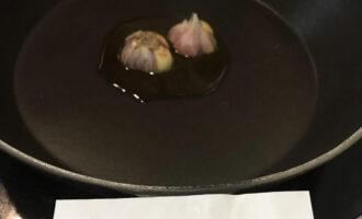 Шаг 2: В сковороду влейте оливковое масло и выложите в него разрезанный поперек чеснок. На среднем огне прижарьте чеснок до аромата и уберите.