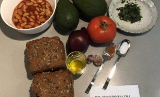 Шаг 1: Подготовьте необходимые ингредиенты: белую фасоль в томатном соусе, авокадо, лимон, цельнозерновой хлеб, лук, помидор, оливковое масло, кинзу, чеснок, перец чили и соль.