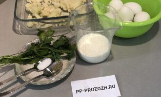Шаг 1: Подготовьте необходимые ингредиенты: заранее размороженную цветную капусту, яйца, молоко, рисовую муку, петрушку, соль и перец черный молотый.