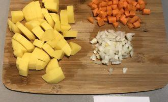 Шаг 3: Пока варится булгур, нарежьте кубиками картофель, лук и морковь.