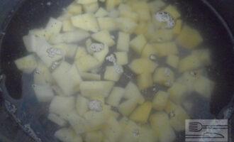 Шаг 3: В кастрюлю влейте воду (1,5 литра). После того, как вода закипит всыпьте картофель. Варите до полуготовности.