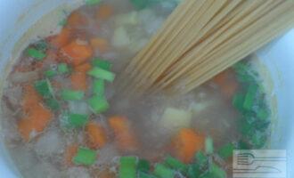Шаг 6: Спустя 15 минут овощи дойдут до полуготовности, а репчатый лук слегка разварится. В почти готовый суп добавьте лапшу вместе с зеленым луком и варите еще 10 минут, периодически помешивая столовой ложкой, чтобы макаронные изделия не слиплись.
