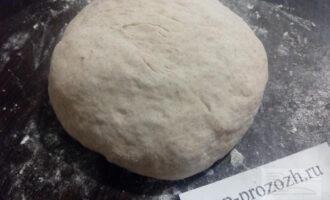 Шаг 4: Оставшуюся муку просейте на стол и замесите мягкое тесто. Оно будет немного липким поэтому потребуется ещё немного муки для формовки пирогов.