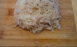 Шаг 3: Картофель натрите на мелкой терке и смешайте с луком.