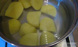 Шаг 2: Очистите картофель, нарежьте на части и поставьте вариться в кастрюле с водой.
