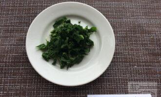 Шаг 6: Опустите листья крапивы в кипяток на несколько секунд. Выньте и остудите. Уберите веточки, оставьте только листья. Нарежьте полосками. Мелко нарежьте зеленый лук.