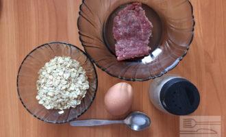 Шаг 1: Для приготовления овсяноблина с мясом возьмите говяжий фарш, овсяные хлопья, яйцо, соль и перец.