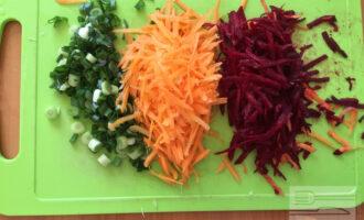 Шаг 3: Морковь и свеклу натрите на крупной терки. А зелёный лук нарежьте мелкими кружочками.