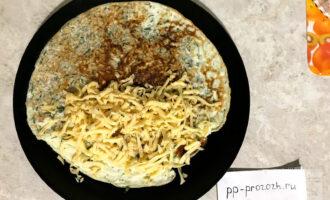 Шаг 5: Горячий овсяноблин выложите на тарелку. С одной стороны присыпьте тёртым сыром и накройте второй горячей стороной.