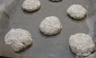 Шаг 4: Сформируйте небольшие сырники, выложите их на противень с пергаментной бумагой. Предварительно сбрызните пергамент растительным маслом.
