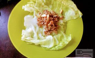 Шаг 4: На отваренные и остывшие листья капусты выкладывайте начинку (примерно столовая ложка с горкой на один лист).