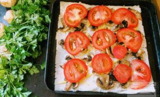 Шаг 5: На лаваш аккуратно укладывайте слоями обжаренное филе, затем грибы, сверху порезанный помидор, сыр.