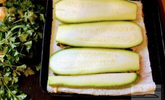 Шаг 6: Порежьте кабачок вдоль, толщиной до пол сантиметра и уложите слой кабачка. Затем сверху опять выложите обжаренное филе, грибы, помидор и сыр.