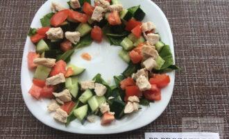 Шаг 5: На тарелку выложите в форме круга салат, на него выложите огурец, помидор и куриное филе.