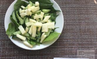 Шаг 3: Яблоко очистите от кожуры и нарежьте полосками. Выложите на тарелку поверх огурцов.