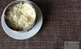 Шаг 5: Затем натрите на тёрке картофель, выложите следующий слой и промажьте майонезом.