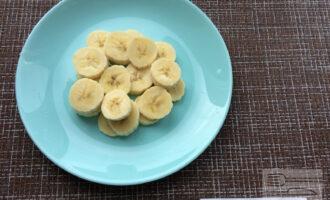 Шаг 2: Банан нарежьте кружочками и выложите в тарелку первым слоем.