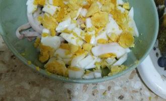 Шаг 3: Яйца почистите и так же нарежьте на полоски. Переложите к кальмару.