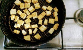 Шаг 3: Нагрейте оливковое масло на сковороде, затем добавьте кусочки тофу и жарьте 5-7 минут.