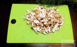 Шаг 4: Грибы мелко порежьте и высыпьте в разогретую и смазанную оливковым маслом сковороду, поджарьте до золотистого цвета. Затем вылейте молоко и высыпьте муку. Тщательно перемешайте и еще готовьте 3-4 минуты до загустения соуса.