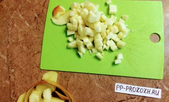 Шаг 3: Яблоко хорошенько помойте, разрежьте на 2 части и вычистите семена, срежьте хвостик и нарежьте кубиками.