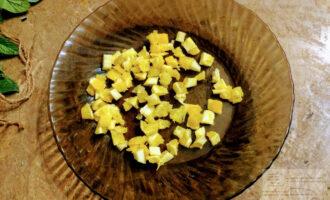 Шаг 2: Возьмите глубокую тарелку. Очистите и нарежьте кубиками апельсин. Уложите в тарелку.