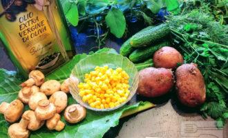 Шаг 1: Для приготовления салата возьмите: картофель, грибы, консервированную кукурузу, огурцы, зелень, соль и оливковое масло.