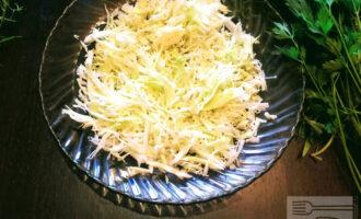 Шаг 3: В глубокую тарелку сложите капусту и помните руками чтобы салат был нежным.