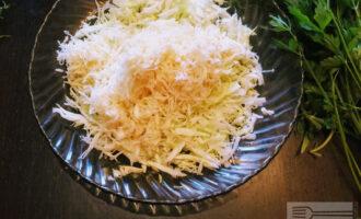 Шаг 4: Сельдерей очистите от кожуры и натрите на терке среднего размера. Добавьте в тарелку с нарезанной капустой.