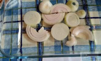 Шаг 4: Лук очистите и нарежьте крупно кольцами или полукольцами и выложите в форму для запекания, смазанную растительным маслом.