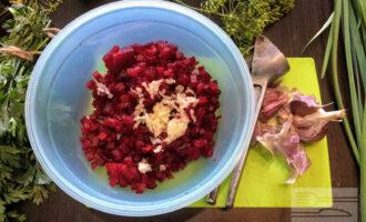 Шаг 5: В глубокую миску переложите порезанную свеклу. Чеснок очистите, измельчите чесночным прессом или мелко нарежьте ножом и добавьте в салат.