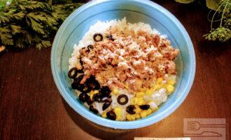Шаг 4: Сардину измельчите вилкой. Возьмите глубокую тарелку и высыпьте рис, маслины, консервированную кукурузу (примерно 2 столовые ложки) и сардину.