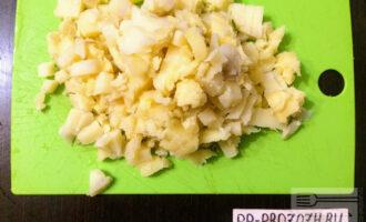 Шаг 4: Вареный картофель мелко порежьте кубиками и уложите половину в форму.