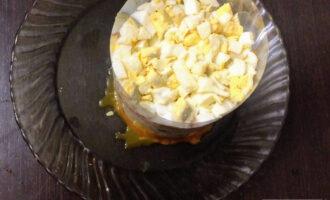 Шаг 8: Яйца нарежьте кубиками и половину уложите в форму, чуть посолите.